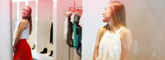 Ung kvinde stående foran et spejl og forsøger nyt tøj. Billede illsutrerar hvordan en ung kvindes krop ændrer sig i puberteten.
