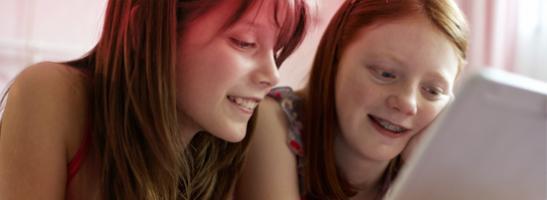Billede af to unge piger sidder foran en computer. Billedet illustrerer at det er almindeligt at have mange spørgsmål og pa o.b.® hjemmeside kan du finde information om den første menstruation, pubertet og andre nyttige oplysninger.
