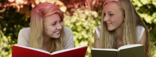 Billede af to unge kvinder der læser en bog. Billedet illustrerer de mange myter forbundet med menstruation.