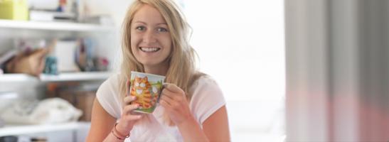 Billede af en ung kvinde med en kop.
