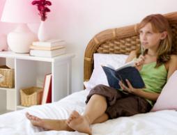 Billede af en ung kvinde sidder på hendes seng og gøre notater. Billedet illustrerer, at der er mange spørgsmål om den første menstruation, men der er intet at bekymre sig om!