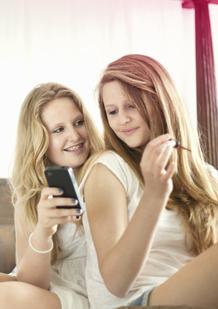Billede af to unge kvinder. En holder en mobiltelefon, den anden lakerer hendes negle med neglelak. Billedet illustrerer at de forandringer, som sker i puberteten, er helt normale og at de er noget, man kan tale om med sine venner eller forældre.